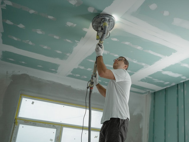 Man polishing any uneven areas of the ceiling.