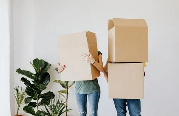 A couple carrying boxes into their new home