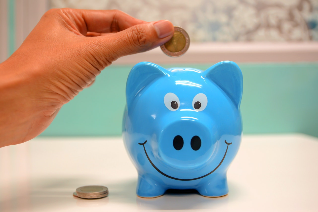 A person putting a coin in a blue piggy bank.